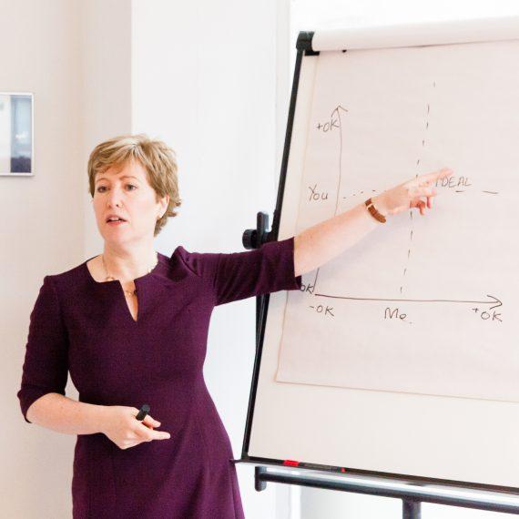 Jude Bainbridge Hamilton gesturing in front of a whiteboard